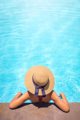 Woman with brown hat relaxing in swimming pool with blue water during a sunny day , holiday concept