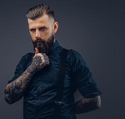 Pensive handsome old-fashioned hipster in shirt and suspenders, pose with hand on chin.