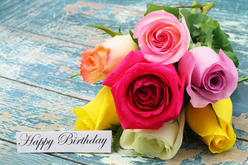 Happy Birthday card with colorful rose bouquet on rustic, blue wooden surface