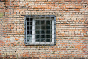 The window behind the iron grate in a brick wall. Prison
