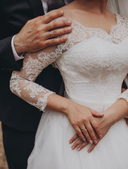 Wedding couple holding hands, groom and bride together on wedding day.