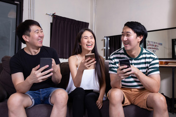 Group of young Asian male and female people smiling and laughing together as using their smart phone at indoors home.