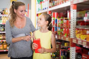 Mom with girl choosing fresh goods in supermarket