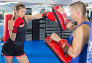 man is training with woman and punching gloves in box gym.