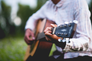 The man's hand plays the acoustic guitar, plays the guitar in the garden alone, happily and loves the music.