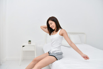 Lifestyle Concept. Asian girls are awake. Beautiful asian woman is relaxing in a white bedroom.