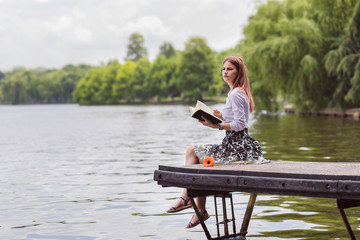 Beautiful girl in a dress with white shirt reading a book and relaxing in park near water. Woman enjoying the weekend. Summer concept of healthy life.