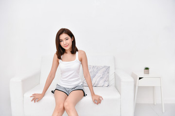 Lifestyle Concept. Beautiful asian woman is relaxing in a white bedroom. Asian girls are playing in the bedroom happily.