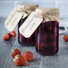 Strawberry jam in glass jar on  gray background.
