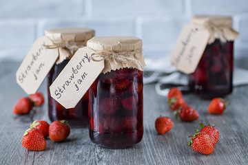 Strawberry jam in glass jar on  gray background.