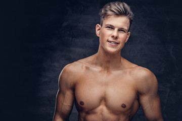 Close-up portrait of a sexy shirtless young man model with a muscular body and stylish haircut...