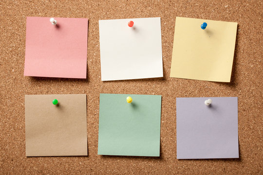 Colorful blank sticky notes on cork board