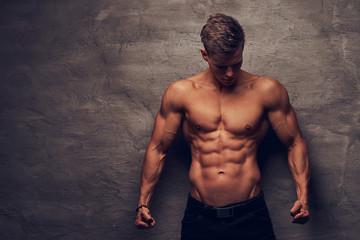 Obraz Beautiful shirtless young man model with nice muscular body posing at a studio. - fototapety do salonu