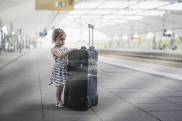 little sweet girl with a large travel suitcase on a deserted railway perforator.