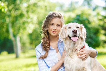 Young woman sitting on the grass with golden retriever dog in the summer park
