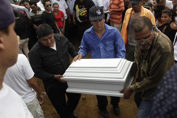 People carry casket containing the body of a person who died after a building caught fire in Managua