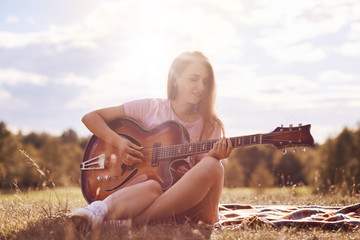 Attractive young female guitarist uses music instrument, plays guitar, sings song, produces wonderful sound or melody, sits crossed legs on plaid, poses against blue sky and sunshine background