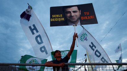 A supporter of Turkey's main pro-Kurdish Peoples' Democratic Party holds a portrait of their jailed former leader and presidential candidate Selahattin Demirtas during a campaign event in Istanbul