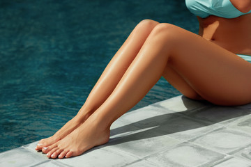 Tan Woman Applying Sunscreen on Legs. Solar cream sun protection concept.
