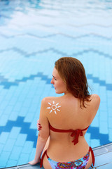 Woman With Suntan Lotion At The Beach In Form Of The Sun. Portrait Of Female With the Drawn Sun On a Shoulder On The Pool
