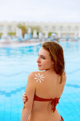 Young woman with sun shape on the shoulder holding sun cream bottle. Female  applying sunscreen. Skincare. Body Sun protection. Bikini  woman smear  moisturizing lotion on back.