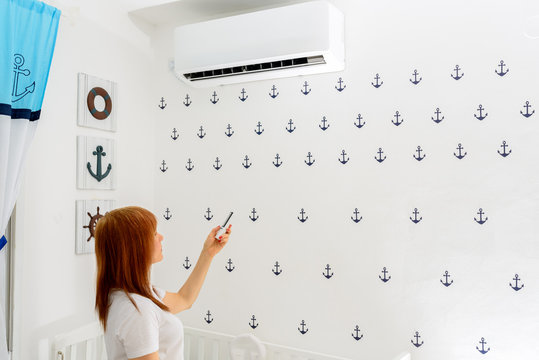 Portrait Of A Happy Woman Holding Remote Control In Front Of Air Conditioner At Home in childrens room.Air conditioner inside the cute baby boy's room.With hot weather,is a good solution for family.