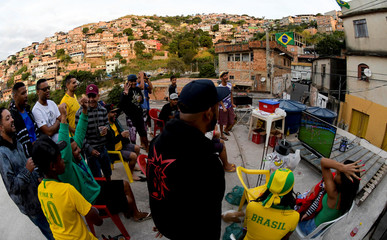 Fans watch the broadcast of the World Cup Group E soccer match between Brazil and Switzerland, at Aglomerado da Serra slum in Belo Horizonte