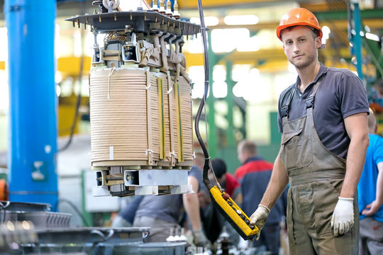 Industrial man worker in factory workshop with conveyor during power transformer assembling by gantry crane