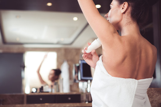 Focus on female hand applying antiperspirant. Young woman standing by mirror in bath towel and holding deodorant in hand. Copy space in left side