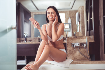 Beauty needs music. Full length portrait of happy young woman sitting on towel with mobile in hands. She is listening to favorite tracks with smile during body care procedures