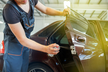 Mechanic lubricates the car, repairs the car door, lubrication spray