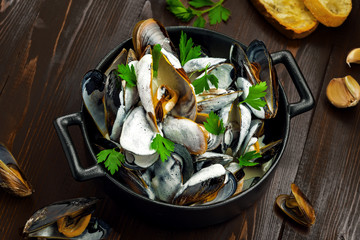 Classic French Mussels cooked with Normande cream sauce. Top view close-up shot.