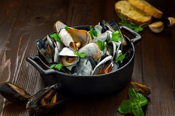 Delicious Steamed Mussels With Wine And Cream on a table. French meal Moules marinière in a bowl.