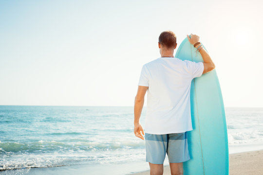 Portrait of happy surfer in hawaiian t-shirt walking with surf board on the beach at sunset
