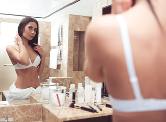 Focus on reflection of beautiful woman in underwear with curious look. She is standing in front of mirror smoothing hair. Make up brushes and cosmetics are lying by mirror