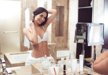 Waist up portrait of attractive young female looking at mirror in bathroom. She is clothed in underwear stroking hair with joy