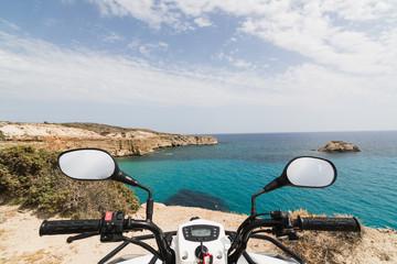 ATV quad bike parked on the shore of Aegean sea on Milos island, Greece
