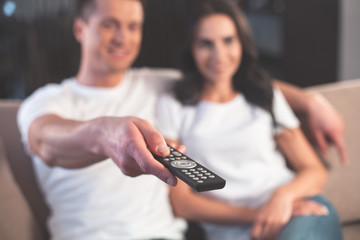 Joyful married couple is watching TV together. They are sitting on comfortable sofa and cuddling. Focus on male hand holding a remote control