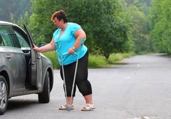 Disabled woman upgoing from a car. Transportation and travel for handicapped people.