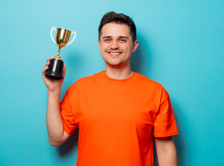 Young handsome man in orange t-shirt with golden cup. Studio image on blue background