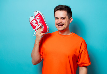 Young handsome man in orange t-shirt with red gumshoes. Studio image on blue background