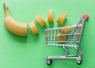 Yellow cut banana with supermarket cart on green background. Natural light