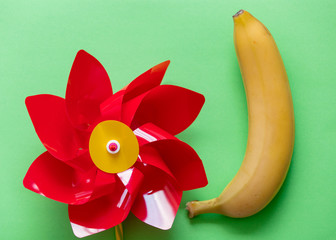 Yellow banana with child pinwheel on green background. Natural light