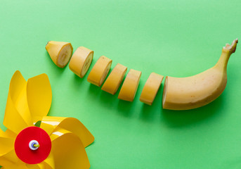 Yellow cut banana with child pinwheel on green background. Natural light