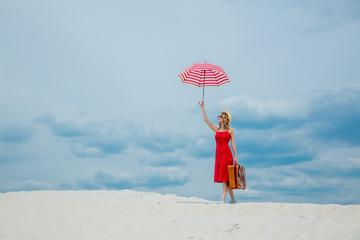 Young woman in red dress with umbrella and suitcase on the beach. Travel concept image on sand