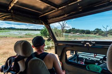 man stop his car and watch beautiful view in safari