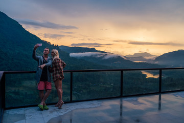couple should be photographed on the terrace on the background of a beautiful sunset in the mountains