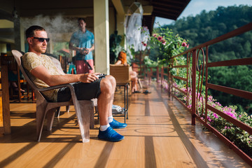 guy sits on a terrace in the highlands and smokes an electronic cigarette