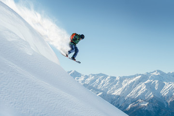 snowboarder jumping on steep mountainside