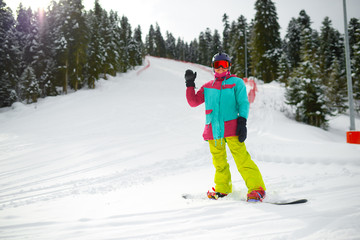 girl snowboarder in gear stands on a slope in the forest